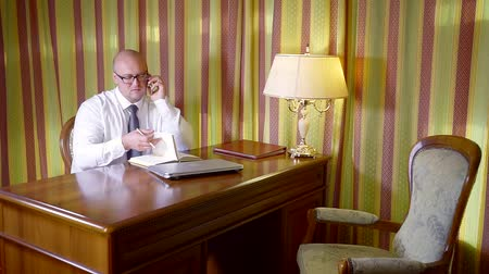 zaměřen : Adult businessman consulting clients on the phone from his office.