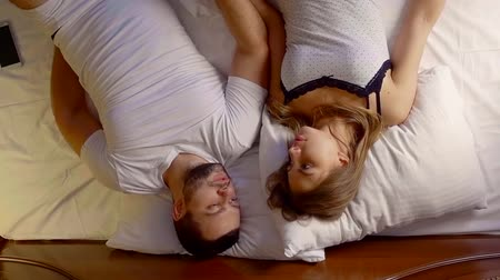 интимный : Upside down shooting of a lovely young couple talking in bed.