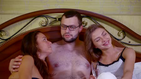sexo : Portrait of a young handsome hot man in glasses laying in bed with sexy girls.