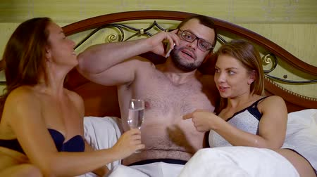 sexo : Successful guy talking on the phone hugging two girl in bed.