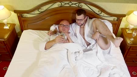 home grown : Two silly men lying in bed together wearing white bathrobes. Stock Footage