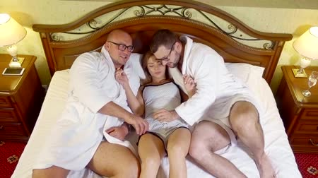 sexo : Two men and one girl in bed at night.