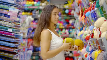 consumir : Handy woman choosing yellow cotton yarn for knitting. Stock Footage