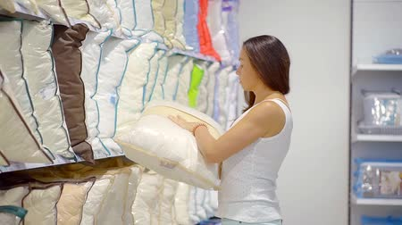 размеры : Female customer choosing new bed linen in the store.