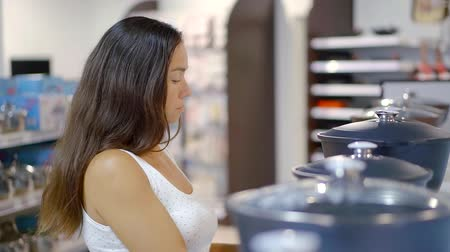 saute : Brunette woman choosing new tableware in the store. Stock Footage