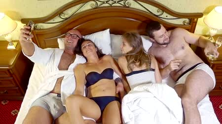 sexo : Two funny couples having fun in bed.