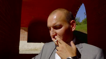 новобрачный : calm and confident groom is smoking cigarette outdoors in sunny summer day, waiting a start Стоковые видеозаписи
