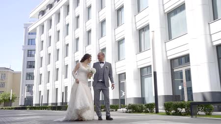 новобрачный : just married couple are walking over street in summertime, smiling and laughing Стоковые видеозаписи
