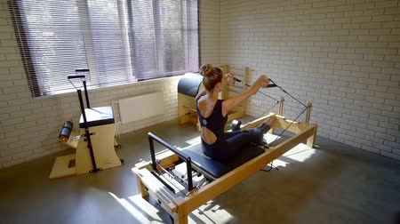 gumka : female gymnast is working out with trainer with elastic ropes, she is pushing plate with body by legs Wideo
