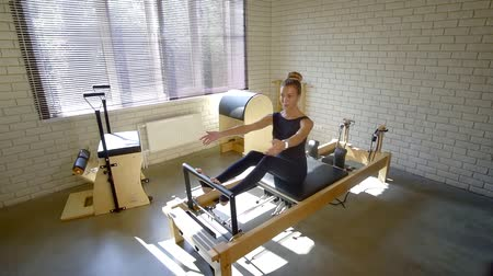 pilates : slim beautiful woman is sitting on a training apparatus in small gym and tensing muscles of legs Stock Footage