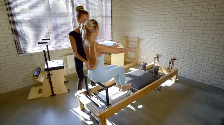 gumka : female fitness instructor is helping young sportswoman is performing exercises with equipment