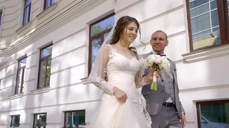 новобрачный : enjoying happy newlyweds are walking in sunny morning over city streets, bride is smelling her flowers