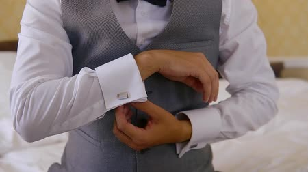 díszgomb : excited young groom is fastening studs on his white shirt, close-up view of his hands, preparing Stock mozgókép