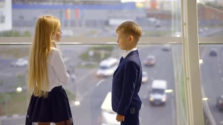 breaktime : smart blonde little girl is speaking with her classmate boy, standing in front of panoramic windows