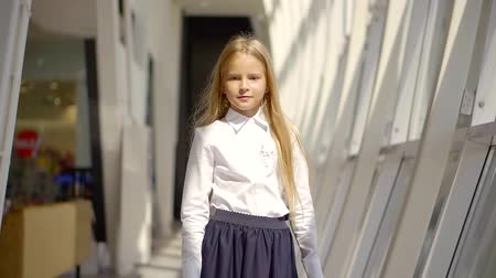 breaktime : pretty little girl is wearing white shirt and black skirt is walking in space of modern school in sunny day Stock Footage