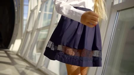 breaktime : little fashionista schooler girl is whirling in sunny hallway of school, close-up view of her skirt