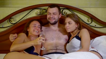 sexo : Portrait of a young handsome hot man in glasses laying in bed with sexy girls. Confident guy spending night with two women in hotel.