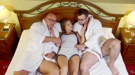 sexo : Two guys having fun with girl in bed of a hotel room. Sexy girl lying between two hot men in bed wearing light shirt. Wild time.