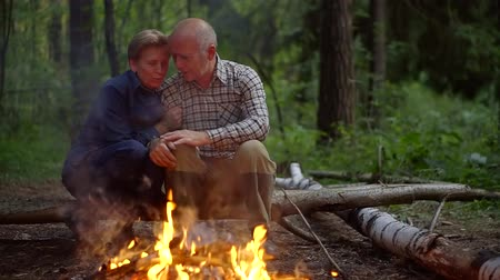 závazek : Happy elderly couple sitting together by the fire on the nature Dostupné videozáznamy