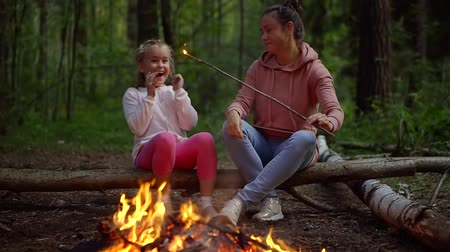 клетчатый : cheerful baby girl and her mom are sitting in the evening in the woods by the fire woman playing with her daughter stick with burning coal