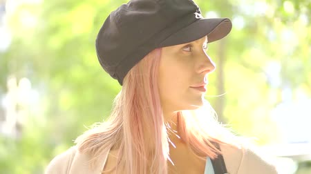 lehkost : Young attractive girl with pink hair and cap on head smiling at camera, glare from sunlight