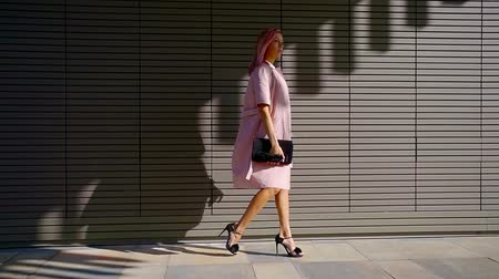 comes : business woman with pink hair comes out of the shade along the wall of a modern building on a Sunny day