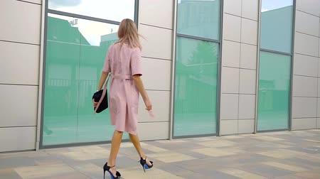 high heeled shoe : wealthy business woman with pink hair and clothes walks along the Mall with large Windows in a green hue