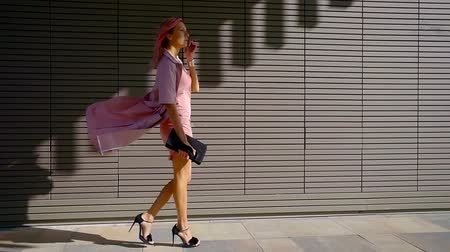 comes : Charming young woman with gorgeous pink hair and stylish appearance. An attractive young lady goes to the city center, on a Sunny summer day. Stock Footage
