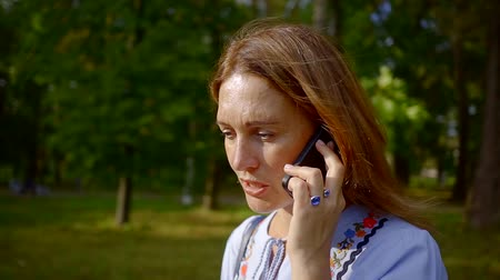 сплетни : middle aged woman is talking by mobile phone in a park in summer evening, she is excited Стоковые видеозаписи