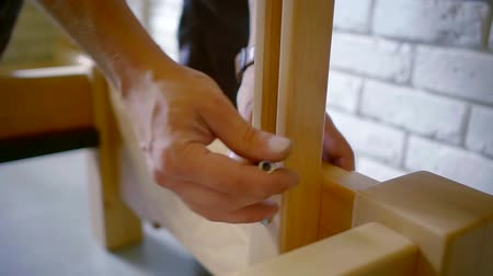 multifunctional : male worker is assembling furniture, he is twisting fastening screw on a wooden beam and taking out Stock Footage
