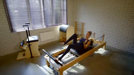 resistência : Beautiful woman adjusting and fixing straps on her legs lying on a moving platform of a reformer machine.