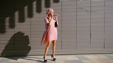 urbanística : fashionista girl is standing on sunny street, putting sunglasses on her face Vídeos