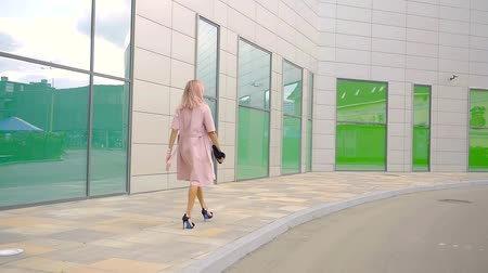 rendkívüli : lovely blonde woman is wearing pink coat is strolling along modern building of business center in summer day Stock mozgókép