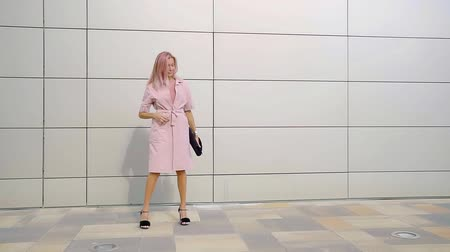 joyfulness : fashion model with pink hair is walking along tiled wall in sunny day, unfastening her coat