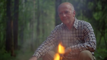 yaşlılar : wise thoughtful old man is sitting alone near fire in forest, his wife is approaching to him, kissing Stok Video
