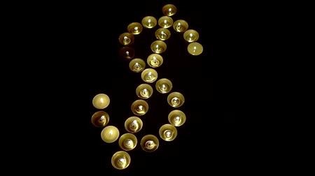 доллар : Top view of candle lights arranged in a shape of a dollar sign.