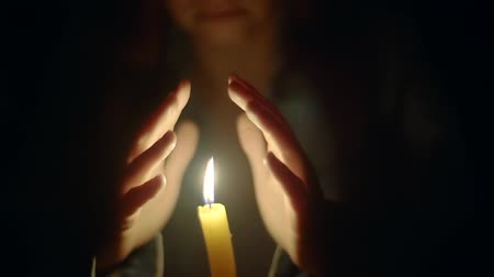 karartmak : woman hands in the dark bask in the flame of a burning candle