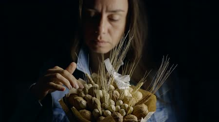 арахис : middle aged pensive woman is holding decorative bouquet from nuts and wheat ears and touching details
