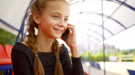 schooler : joyful little school girl is talking by mobile phone in a hallway, she is smiling and swaying head