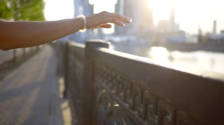 handrails : female hand is touching by fingers a fence of embankment in city in sunny day, close up