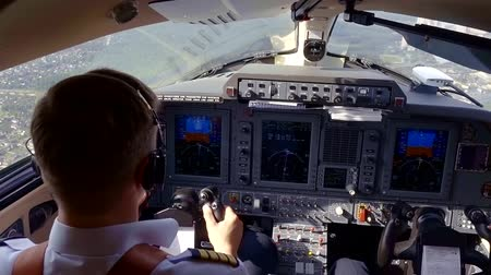 pilot in command : View from behind of a captain of plane and a pilot in flight deck, crew flying over cities, beautiful view out of windshield.