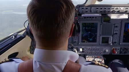 pilot in command : Close-up shot of a captain of aircraft piloting in cockpit, serious and responsible job. Stock Footage