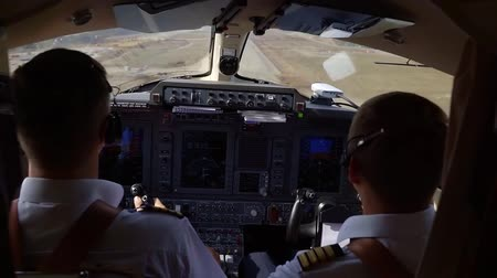 pilot in command : Shot from behind of two male pilots landing a plane in airport, runaway. Stock Footage