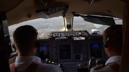 first officer : View from behind of two pilots in cockpit flying a plane, control panel with buttons and switches.