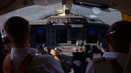 pilots : small military airplane is flying over landscapes, view from cabin of pilot, two airmen are directing plane