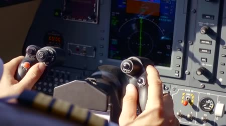 индикатор : airman hands are holding a control of aircraft, close-up in a cabin of small airplane, monitor and buttons