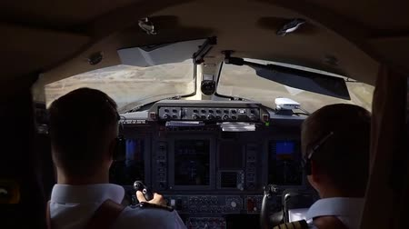 kapitán : two pilots are landing an aircraft, back view of them and on a runway of small aerodrome