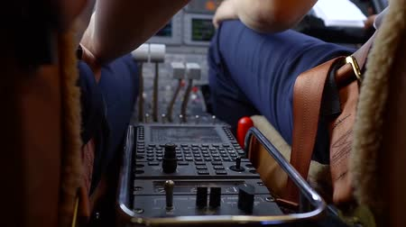 construir : pilots in a cabin of small aircraft are preparing to flight, checking systems and adjusting, close-up of hands