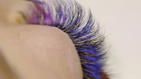 иностранец : Close-up of the female eye . demonstration of volumetric multi-color eyelash extension on the girl model Стоковые видеозаписи