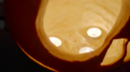 korkunç : Terrible carved pumpkin for Halloween. close-up of candles in vegetable Stok Video